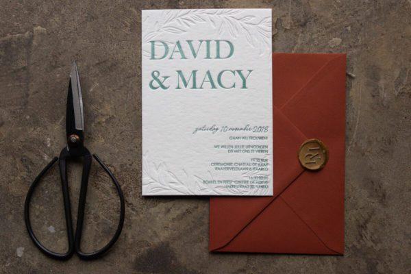 Letterpress trouwkaart met bladeren verdiept in papier gedrukt