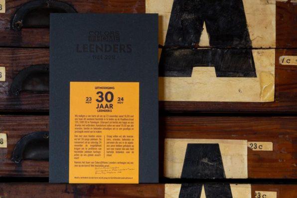 Uitnodiging gedrukt op dik papier met gele wikkel